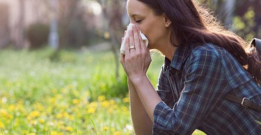 Woman Blowing Nose in Field